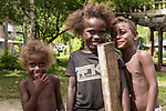Peava Village, Gatokae Island, Solomon Islands; three children pose for a photo in their village