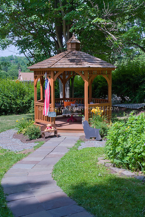 Gazebo and American flag, path walkway, blue sky, dog statue, daylily, lawn grass