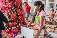 STAFF PHOTO ANTHONY REYES &bull; @NWATONYR<br /> Anaha Canales, 13, student from Tyson Middle School, carries a box of donated food Tuesday, Dec. 16, 2014 at the school in Springdale. Canales and several other students at the school organized all the doanted food. The school collected non-perishable food items to be given to local agencies and families at the school in need.