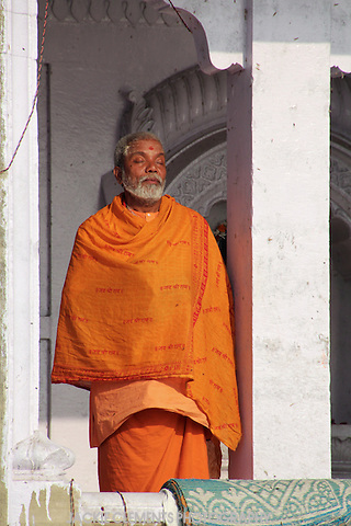 A man wrapped in orange Hindu robes basks blissfully in the early morning sun by the holy Ganges River