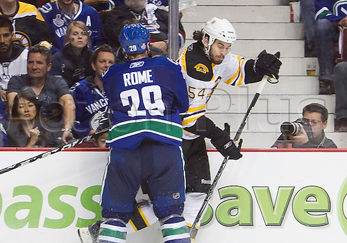 01.06.2011.  Second Period - Adam McQuaid (54) of the Bruins  collides with Aaron Rome (29) of the Canucks  during Game (#1) of the Stanley Cup Finals between the Vancouver Canucks and the Boston Bruins held at Rogers Arena in Vancouver, British Columbia, Canada.