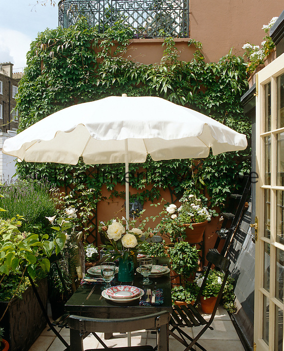 A lunch table on a narrow roof terrace is shaded from the sun by a white parasol