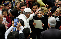 Pope Francis greets a child as he arrives to attend his weekly general audience in the Paul VI hall at the Vatican, January 22, 2020.<br />