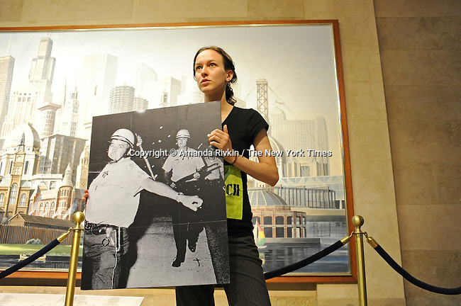 An activist with Cop Watch holds up a poster of Chicago police officers in riot gear at a press conference of activists opposed to the 1968 Riot Cops Reunion in a hallway at City Hall in Chicago, Illinois on June 23, 2009.