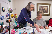 NWA Democrat-Gazette/BEN GOFF @NWABENGOFF<br /> Joyce Kerr of Gravette helps Shirley Gaw of West Siloam Springs, Okla. explore designs to decorate her egg Friday, March 22, 2019, during a Ukrainian Easter egg decorating class at the Gentry Senior Activity Center. Kerr and husband Kent Kerr lead the class on decorating eggs using wax to make designs and dips into multiple colors of dye to create eleborate designs. The senior activity center holds a craftmaking class each Friday.