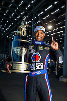 Nov 12, 2015; Pomona, CA, USA; NHRA top fuel driver Antron Brown poses for a portrait with the 2015 championship trophy prior to qualifying for the Auto Club Finals at Auto Club Raceway at Pomona. Mandatory Credit: Mark J. Rebilas-USA TODAY Sports