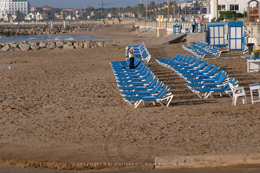 The beach. Rows of empty deck chairs. A man cleaning. Sitges, Catalonia, Spain