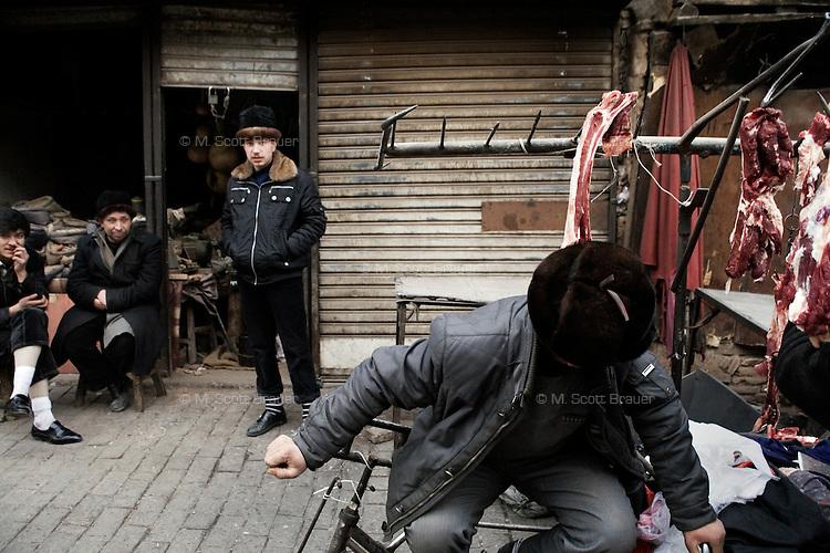 Uighur men stand near a butcher stand in Kashgar, Xinjiang, China.