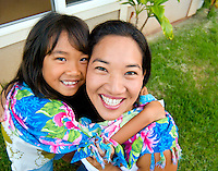 Local part Hawaiian mother and daughter in yard in front of their home in Makakilo, Oahu