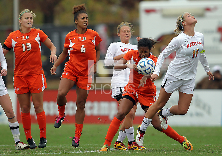 COLLEGE PARK, MD - OCTOBER 28, 2012:  Olivia Wagner (11) of the University of Maryland flips the ball backwards towards Blake Stockton (29) of Miami during an ACC  women's tournament 1st. round match at Ludwig Field in College Park, MD. on October 28. Maryland won 2-1 on a golden goal in extra time.