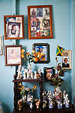 JAMAICA, Port Antonio. Family photos on a wall inside a local home.