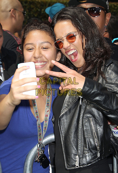 Michelle Rodriguez<br /> &quot;Turbo&quot; Party And Pop-Up Concert During E3 Gaming Convention held at Nokia Theatre L.A. Live, Los Angeles, California, USA.<br /> June 12th, 2013<br /> half length top leather jacket black sunglasses shades mouth open hand v peace sign fan posing taking picture photograph <br /> CAP/ADM/RE<br /> &copy;Russ Elliot/AdMedia/Capital Pictures