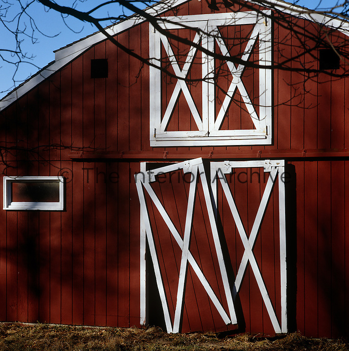 A door on this traditional red and white clapboard barn has fallen off its rail and hangs crookedly