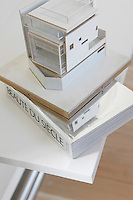Perched on a book whose title might describe the building itself, a cardboard maquette of the house by Pablo Katz