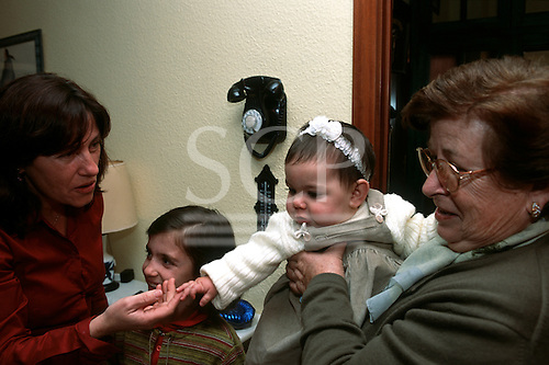 Seville, Spain. Three generations: mother, grandmother, daughter and baby with a telephone and a thremometer on the wall.