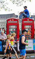 17 APR 2011 - LONDON, GBR - A spectator uses two of London's famous red telephone boxes to give himself a good viewpoint of the 2011 London Marathon (PHOTO (C) NIGEL FARROW)