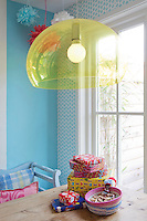 A second lamp, this time with a transparent yellow shade, hangs above the table, contrasting with the pale blue walls of the kitchen