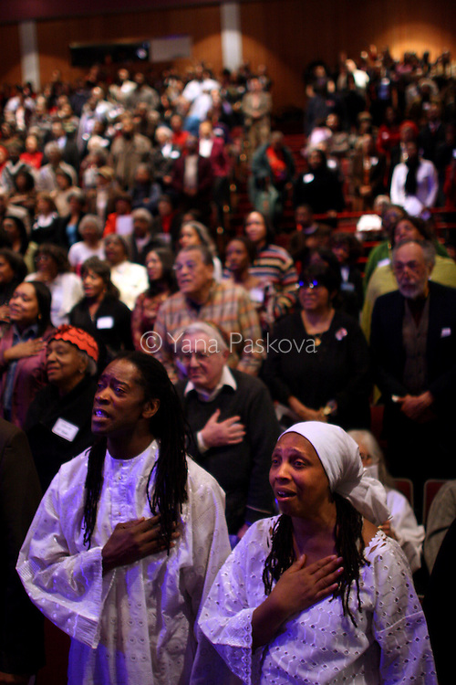 "(L-R) Malik Camara, 47, teacher, and Stephanie Davenport, Director of Education at DuSable, (both from Chicago,) sing the American national anthem while watching the inauguration of Barack Obama as President of the United States in the theater of the DuSable Museum of African-American History in Chicago, Illinois, on the Presidential Inauguration Day, Tuesday, January 20, 2009.  Camara said, ""I expect Obama to stay grounded, spiritually, mentally, and physically, because a lot in his job will be overwhelming, but as long as he stays grounded, he will be okay."" Camara's phone number: 773.239.1771 (Photo by Yana Paskova for The New York Times)..Assignment ID: 30075164A"