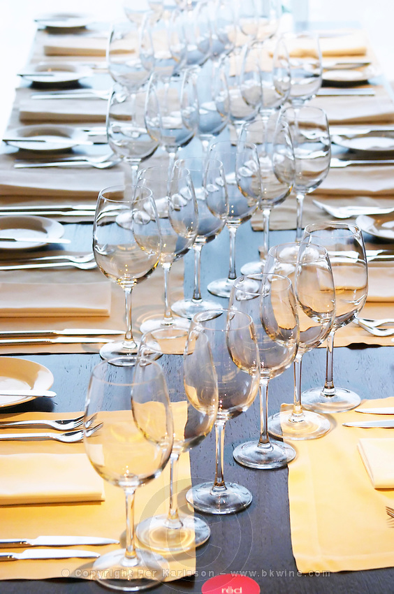 A table set for lunch with many glasses for wine tasting diagonally on a black wooden table. The Restaurant Red at the Hotel Madero Sofitel in Puerto Madero, Buenos Aires Argentina, South America