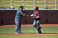 Jakob Divers (2) of the Concord Mountain Lions shakes hands with third base coach Devin Smith after hitting a home run against the Wingate Bulldogs at Ron Christopher Stadium on February 2, 2020 in Wingate, North Carolina. The Mountain Lions defeated the Bulldogs 12-11. (Brian Westerholt/Four Seam Images)