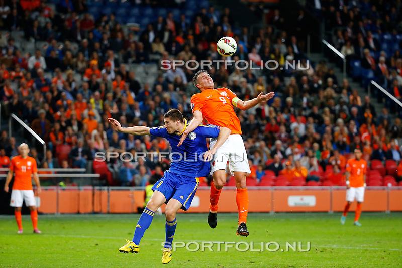 Nederland, Amsterdam, 10 oktober 2014<br /> Seizoen 2014-2015<br /> EK Kwalificatiewedstrijd <br /> Nederland-Kazachstan <br /> Robin van Persie van Nederland en Viktor Dmitrenko (l.) van Kazachstan strijden in een kopduel om de bal.
