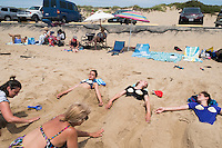 Sisters Chloe, 15, (center) and Amelie Lachance-Soulard, 16 (right), of Ottawa, Canada, and cousin Simone Soulard, 14, lay buried under sand sculptures of mermaid tails at Herring Cove Beach in the Cape Cod National Seashore outside of Provincetown, Mass., USA, on Fri., July 1, 2016. Their aunt Claudine Soulard, of Montreal, (at right in lower left) and the sisters' mother Pascale Lachance, of Ottawa, (lower left) helps sculpt the sand. Portions of the parking lot have been closed after land eroded during storms earlier this year. This was the girls' first visit to the area.