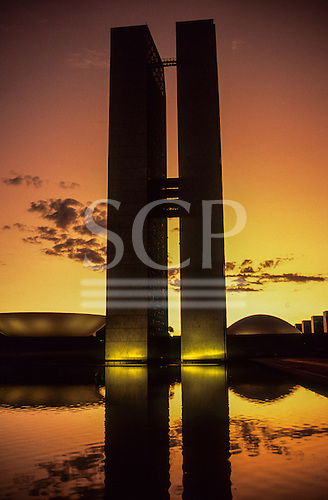 Brasilia, DF, Brazil. National Congress buildings by architect Oscar Niemeyer; twin towers and the dome and dish at dusk, Praca dos Tres Poderes.