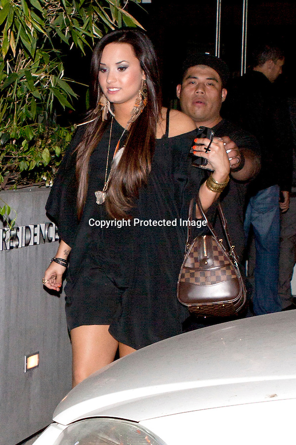 June 4th 2011..Demi Lovato fresh out of rehab leaving the Café Entourage bar in Los Angeles.Feather earrings and necklace orange finger nails short black dress fat chubby thick legs thighs tattoo arm wrist cuts checkered brown louis vuitton purse handbag double finger cross ring ..Abilityfilms@yahoo.com.805-427-3519.www.Abilityfilms.com..