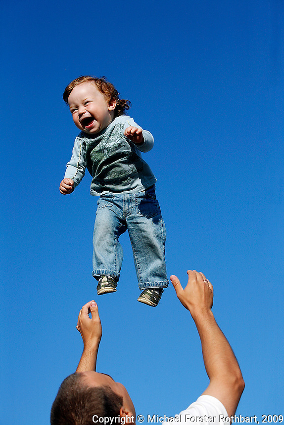 Andrei Balta throws his fifteen-month-old son Vanya in the air during a summer evening in Slavutych, Ukraine. Andrei and his wife Anna both work at the nearby Chernobyl Nuclear Power Plant, as do over 3,800 residents of Slavutych. <br /> ------------------- <br /> This photograph is part of Michael Forster Rothbart's After Chernobyl documentary photography project.<br /> &copy; Michael Forster Rothbart 2007-2010.<br /> www.afterchernobyl.com<br /> www.mfrphoto.com <br /> 607-267-4893 o 607-432-5984<br /> 5 Draper St, Oneonta, NY 13820<br /> 86 Three Mile Pond Rd, Vassalboro, ME 04989<br /> info@mfrphoto.com<br /> Photo by: Michael Forster Rothbart<br /> Date: 7/2009    File#:  Canon 5D digital camera frame 72371<br /> ------------------- <br /> Original caption: .Andrei Balta throws his fifteen-month-old son Vanya in the air during a summer evening in Slavutych, Ukraine. Every evening, parents with babies and toddlers gather in the central square of Slavutych to socialize. Andrei and his wife Anna both work at the nearby Chernobyl Nuclear Power Plant, as do over 3,800 residents of Slavutych.