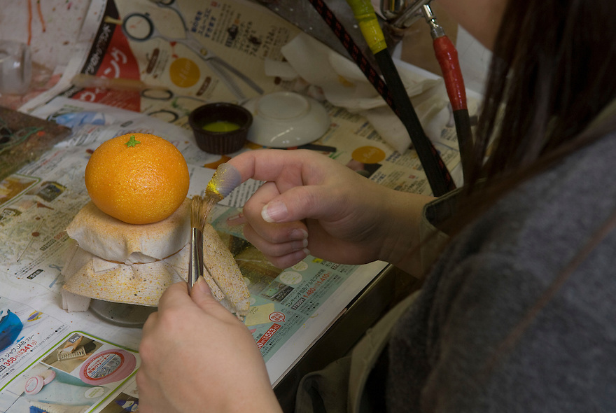 Painting a plastic mandarin orange at Maiduru Corporation, Tokyo, Japan, 22nd December 2008. Maiduru corporation makes highly realistic plastic food for display in restaurant and cafe windows. .
