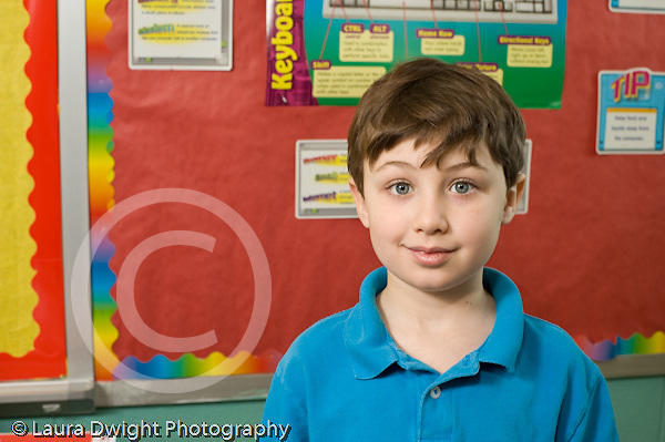 Education Elementary school Grade 2 closeup portrait of male student colorful bulletin board behind him horizontal