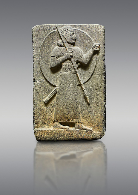 Picture & image of Hittite relief sculpted orthostat stone panel of Royal Buttress. Basalt, Karkamıs, (Kargamıs), Carchemish (Karkemish), 900-700 B.C.  Warrior.  Anatolian Civilisations Museum, Ankara, Turkey.<br /> <br /> The figure with a long dress, a thick belt and curly hair has a large egis on his back. The figures carries a spear in his right hand and a long sword at his waist.  <br /> <br /> Against a gray background.