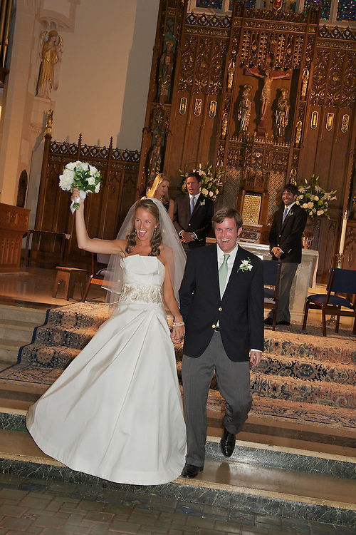 An exuberant bride and groom walking down the steps of the altar right after the ceremony.