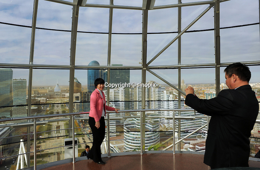 Tourists take photos in the dome of the  most famous building in Astana the Bayterek in Astana, the capitol of Kazakstan.<br />