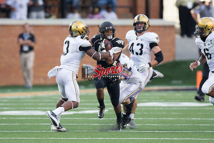 Orville Reynolds (5) of the Wake Forest Demon Deacons is hit by Josh Jenkins (3) and Jeremy Timpf (39) of the Army Black Knights at BB&T Field on September 20, 2014 in Winston-Salem, North Carolina.  The Demon Deacons defeated the Black Knights 24-21.  (Brian Westerholt/Sports On Film)