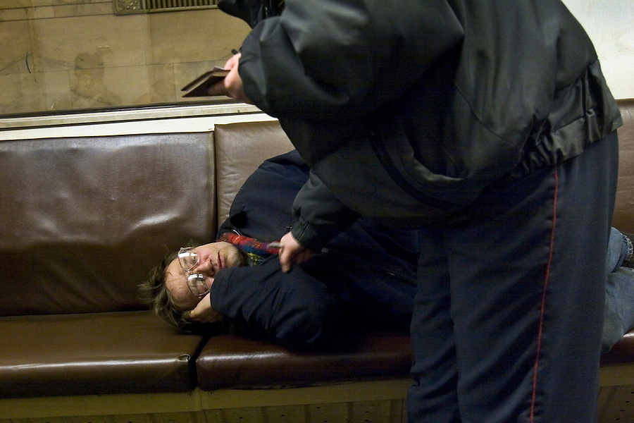 Moscow, Russia, 17/01/2006..Police arrest a homeless man sleeping in a metro carriage as a Siberian weather front brings temperatures down to minus 36C in the Russian capital and leads to power cuts in the city. Many of Moscow's estimated 10,000 homeless seek shelter in the metro and subways during the fierce Russian winter.