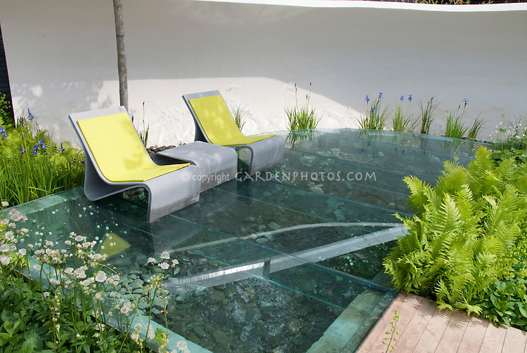 Water garden feature and unusual clear plastic deck patio, blue iris, ferns, Euphorbia, modern chairs furniture, white privacy wall, for blue and yellow and green serene garden color theme in spring