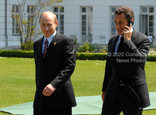 Heiligendamm, Germany - June 7, 2007 -- President Vladimir Putin of Russia and President Nicolas Sarkozy of France (on the phone) walk together on the way to the wicker beach chair at the G-8 Summit in Heiligendamm, Germany on Thursday, June 7, 2007..Mandatory Credit: BPA via CNP