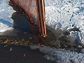 A late-winter thaw creates a slushy mess near a snow fence.