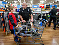 NWA Media/JASON IVESTER --12/09/2014--<br /> Benton County Sgt. Jorge Keene talks with Dylan Williams, 10, of Bentonville while shopping for clothes and toys on Tuesday, Dec. 9, 2014, inside the Wal-Mart Supercenter on Pleasant Crossing Boulevard in Rogers. Members of the Benton County Sheriff's Office helped the children pick out clothes and toys with a $150 budget each as part of the department's annual Shop With a Cop program.