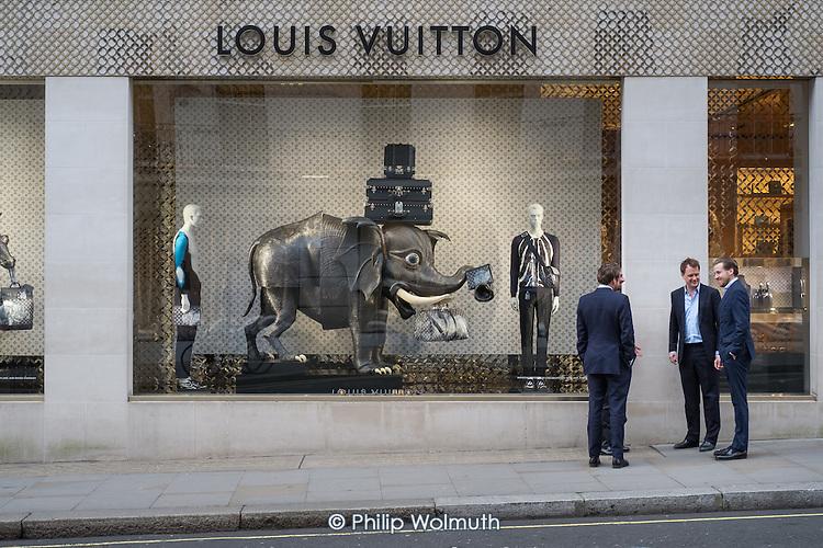 Men in suits outside Luis Vuitton  luxury shop, Mayfair, London.
