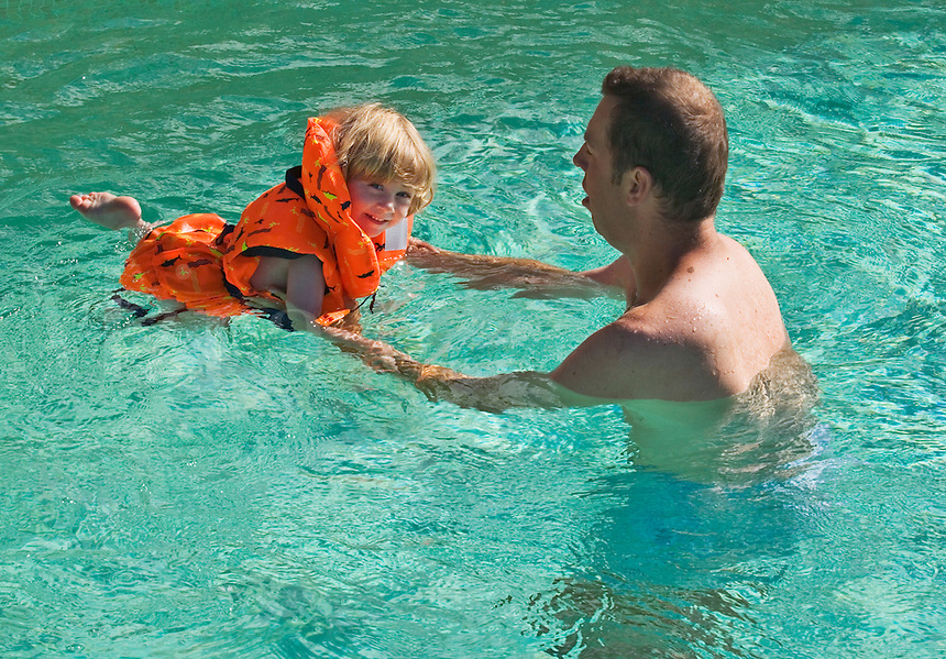 Father teaches his 28 month old daughter to swim.  Girl wearing a life vest. Model released.