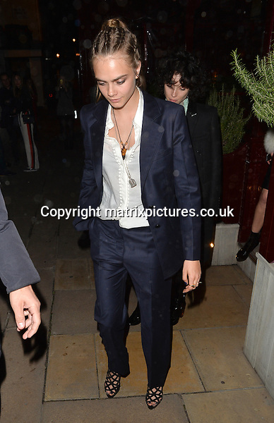 NON EXCLUSIVE PICTURE: PALACE LEE / MATRIXPICTURES.CO.UK<br /> PLEASE CREDIT ALL USES<br /> <br /> WORLD RIGHTS<br /> <br /> English model and actress Cara Delevingne is pictured visiting Loulou's restaurant in Mayfair, London. <br /> <br /> The 23 year old, who flashed her flesh wearing a skimpy LBD at the Pan premiere earlier on in the evening, looks more conservative in a navy blue trouser suit. <br /> <br /> SEPTEMBER 20th 2015<br /> <br /> REF: LTN 152924