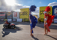 Oct 30, 2016; Las Vegas, NV, USA; Las Vegas Showgirls react as heavy winds blow while NHRA pro stock motorcycle rider Andrew Hines heads back to the pits during the Toyota Nationals at The Strip at Las Vegas Motor Speedway. Mandatory Credit: Mark J. Rebilas-USA TODAY Sports