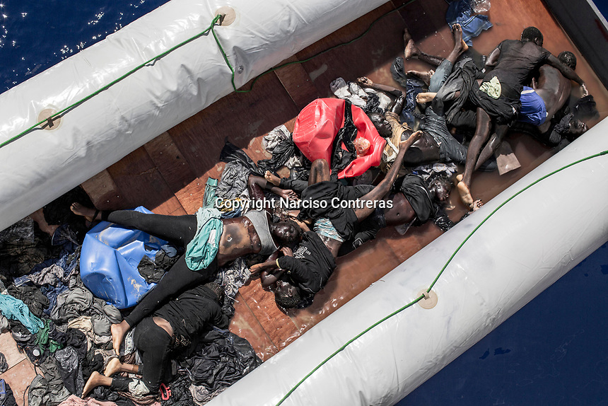 The corpses of illegal Sub-Saharan African migrants lie at the bottom of a dinghy boat after being recovered by Santa Lucia merchant ship in the Mediterranean Sea. Four rubber dinghies and some 500 survivors in total were being pulled to safety on that day.
