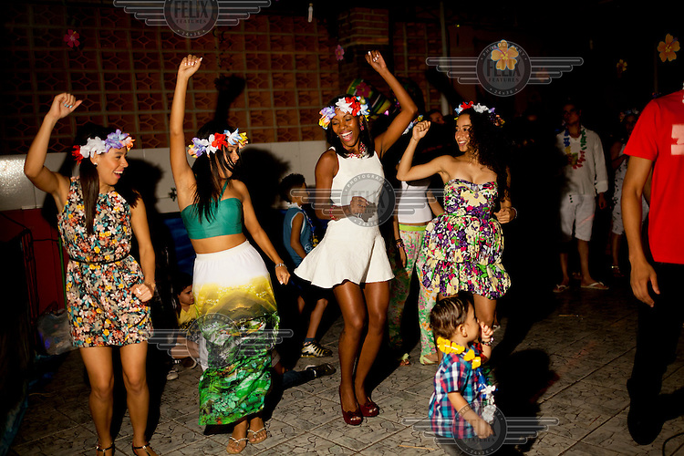 Friends dance at a birthday party in Complexo da Mare. The favela consists of a complex of 16 communities, in the north zone of Rio de Janeiro. It is the largest complex of favelas, housing 130,000 residents. It is targeted for pacification as the city prepares for the 2014 World Cup and the 2016 Olympics. Four factions run the complex, three drug gangs and the militia. The rival gangs fight for control of the drug trade. Although crime is low in the favelas by rule of law enforced by the gangs, cross-fire shootings and gang violence is often high. Neighborhood associations are an integral part of community development within Mare, making up for a lack of government assistance.