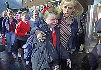 Children, some close to tears, are escorted by their parents past a picket line of Protestant protesters on their first day back to Holy Cross Roman Catholic Primary School for Girls, Belfast. As a result of the Troubles an area that was previously fairly well integrated became completely polarised and the school found itself in a completely Protestant area. The picket was prompted by Protestants claiming that Roman Catholics were regularly attacking their homes and denying them access to local facilities. 200109034602<br />