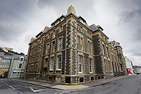 Pictured: Front-side view of the old Police Station in Aberystwyth, Wales, UK. Wednesday 28 August 2019<br /> Re: Opened 1866, built by the Hafod Hotel Co as the Queens Hotel; architects, Hayward and Davies; builder George Lumley of Aberystwyth. Sold in 1877 and later converted to local government use; remodelled in1950 by G R Bruce, County Architect.<br /> Detached towards N end of the Promenade, with main entrance to side elevation in Albert Place and rear elevation to Queens Road.<br /> Hotel de Ville style. Asymmetrical 3-storey attic and basement snecked rubble 13-bay W (Promenade) elevation; stepped front with mostly vermiculated dressings, stock brick voussoirs, deep entablature and cornice and cill bands; buttresses to ground floor centre. Steep pitch mansard slate roof with truncated chimney stacks. Dormers with steep overhanging roofs and casement windows; paired to left. 3-bays advanced near the right hand end and with additional storey and splayed angles to 2nd floor (with small cast-iron parapets) and 3rd floor; also to top floor) with small cast-iron parapets) and 3rd floor; also to top floor at the corner. Sash windows, some paired; anthemion panelled cast-iron window box holder across central bays.