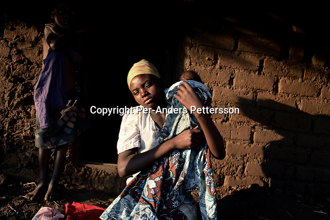 GALUFU, MALAWI NOVEMBER 16: Silvea Samael, age 17, holds her one-month old baby girl Emily outside her house on November 16, 2005 in Galufu, Malawi. Silvea has the last years sold her body for sex to men in the village and other villages due to the extreme poverty she faced. She thought being pregnant would solve her problems but they have increased, as she doesn't know who the father is, and she had to quit school. She usually sells her body for soap, oil for the face or a very little money. The village has seen an increase in poverty the last few years due to drought and HIV/Aids. Alina harvested a bag (about 25kg) of maize during 2005 and the food only lasted for a few weeks. Southern Africa has been hit by a severe hunger crisis due to drought and poverty. An ever-increasing HIV/Aids rate adds to the misery. Malawi is one of the worst hit areas and Galufu village is a typical small village that has become victim of this poverty spiral. <br /> (Photo by Per-Anders Pettersson)