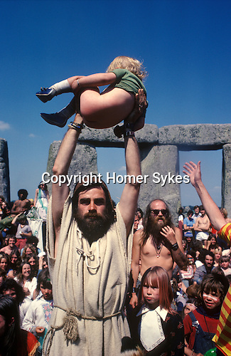 Bev Richardson or Pagan Bev. 1970's style hippies attend the second free festival at Stonehenge to celebrate the summer solstice June 21st 1979. This boy has just been baptised.